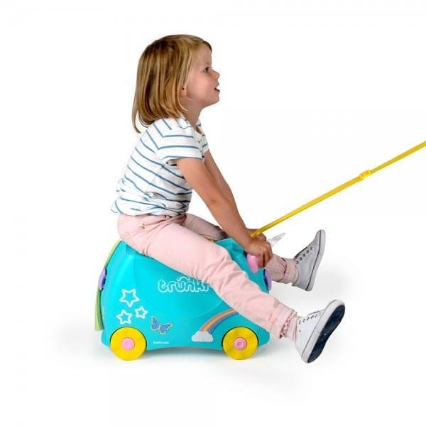 Menina montada na mala Trunki unicórnio sendo puxada