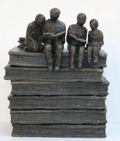 familia lendo sentada em uma pilha de livros